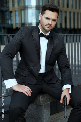 фотография  Elegant man with a gun in his hands sits on the background of the city