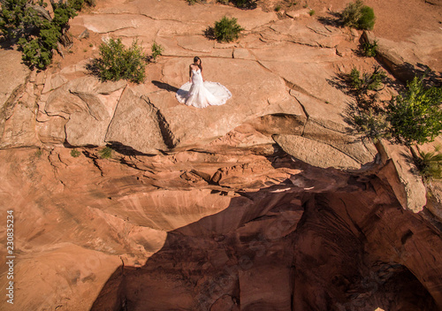 Fotografía Aerial/Drone Wedding photo of a Bride in her wedding dress on a cliff overlooking a massive sinkhole in the Utah Desert, near Moab