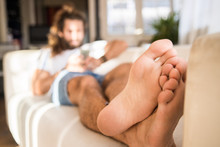 Man Laying On A Sofa Showing His Feet