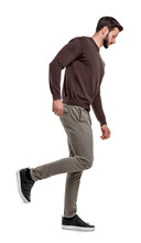 A Serious Looking Man In Casual Clothes Walks In A Side View With One Leg Bent Up Behind Him.