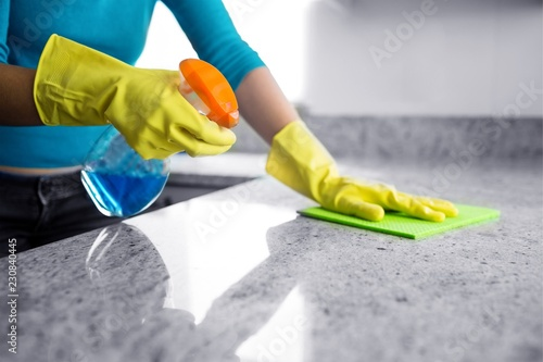 Obraz Mid section of woman cleaning kitchen counter - fototapety do salonu