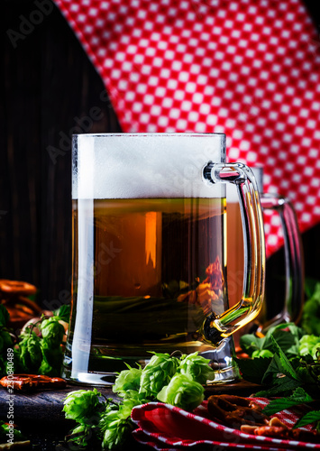 Foto op Aluminium Bier / Cider Light german beer poured into big glass, fresh green hops and bowls with salty snacks and nuts, autumn beer festival concept, dark background, selective focus