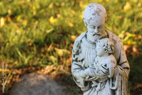 Fotografie, Obraz  Religious statue on gravestone in cemetery