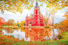 Bad Muskau Park And Palace - Famous UNESCO World Heritage Site In Germany And Poland. Amazing Seasonal Autumn Landscape With Reflections Of Great Classic Architecture In Pond Waters. Yellow Leaves.
