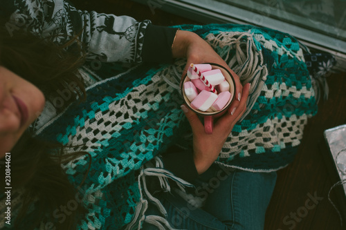 фотография  Loneliness christmas - girl sitting alone holding cup with marshmallow in a hands