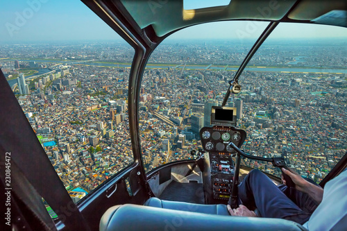 Tuinposter Helicopter Helicopter cockpit inside the cabin flying on Tokyo cityscape. Sumida District, Japan. Sunny day.