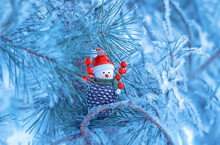Toy Snowman On The Winter Pine Tree. Christmas Greeting Card With Xmas Tree And Toy. Soft Selective Focus.