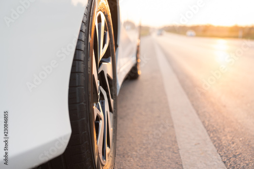 Photo  Close up wheel of white cars on the road.
