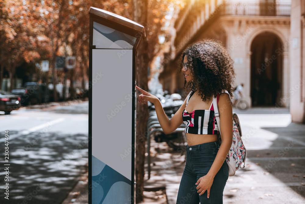 Fototapeta Young curly caucasian female hipster is paying for parking using outdoor electronic pay station terminal; charming Brazilian woman using an automatic street kiosk to finish her parking payment