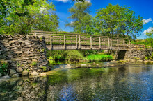 A Wooden Footbridge Crossing A River In The English Lake District.