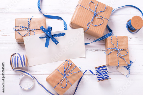 Empty tag and wrapped gift boxes with presents and blue ribbon on textured wooden background.
