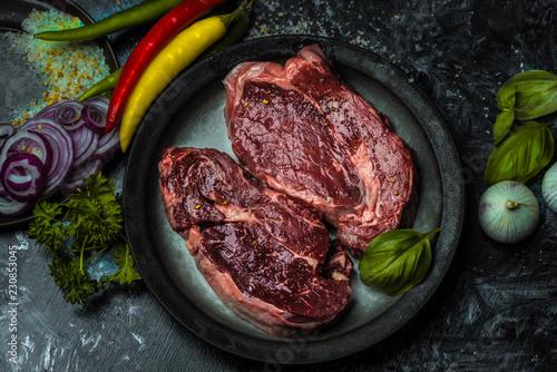 Cadres-photo bureau Steakhouse on a dark background fresh, red, raw beef and spilled coarse salt, next to it lies fresh vegetables