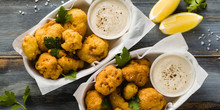 """Banner Of Fried Cauliflower In Batter With A Savory Sauce Of Cashew Nuts. Healthy Vegan Fast Food. Baked Buffalo Cauliflower """"wings"""" On Blue Wooden Background"""