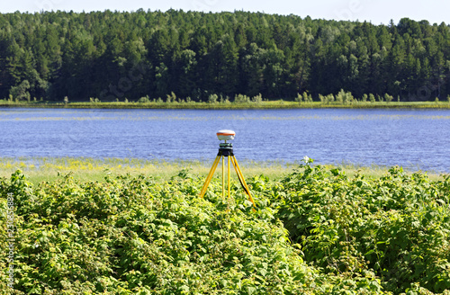 Fotografie, Obraz  Geodetic GNSS receiver installed on the river bank works autonomously
