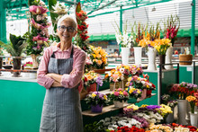 Portrait Of Senior Woman Sales Flowers On Local Flower Market