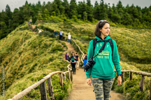 Foto  Young woman in khaki clothing is standing on the most popular place on Azores islands - Miradouro da Boca do Inferno