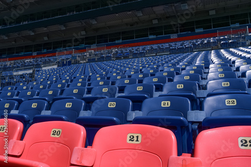 Fotografie, Obraz  Empty rows and sections of red and blue seats in a sports stadium