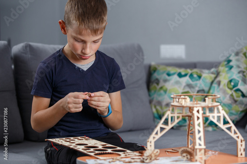 Fotografie, Tablou  Young boy playing with eco wooden constructor