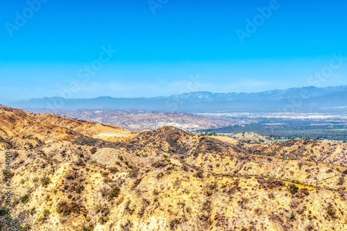 Dry foothills with house development and suburbs in the distant