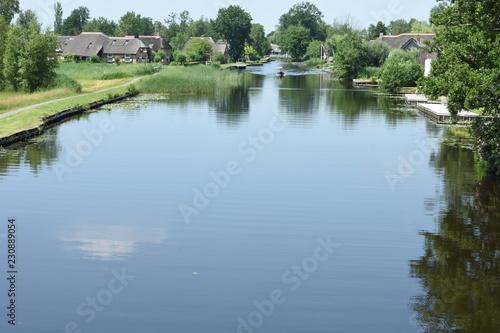 Fotografie, Obraz  beschoeid kanaal met fietspaden en boerderijen met rieten daken aan weerszijden