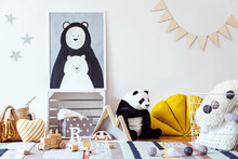 Stylish Scandinavian Kid Room With Mock Up Photo Poster Frame On The Pattern Wall, Boxes, Teddy Bear And Toys. Cute Modern Interior Of Playroom With White Walls, Wooden Accessories And Colorful Toys.