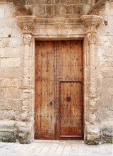 Large Old Brown Wooden Door Covered With Rusted Iron Studs Keyhole And Handle Set In An Ornate Carved Stone Frame With Surrounding Wall