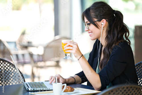 Fotografie, Obraz  Beautiful young woman drinking orange juice while working with her laptop in a coffee shop