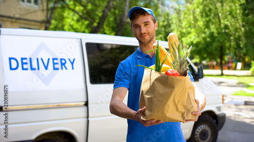 Photo Delivery company worker holding grocery bag, food order, supermarket service