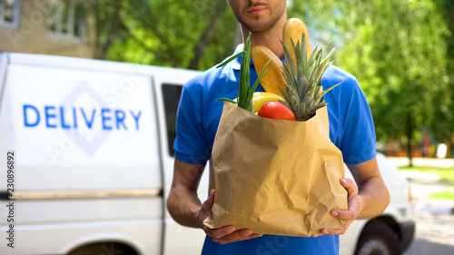 Food delivery service, male worker holding grocery bag, express food order Canvas Print