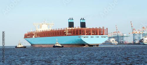 Tuinposter Poort Containerschiff legt an den Containerbrücken im Containerhafen von Bremerhaven an, Anlegemanöver mit Schleppern