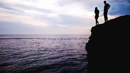 Loving couple standing on edge of rock, preparing for jump into water, romantic