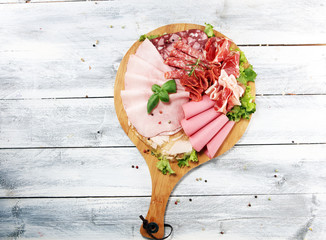 Fototapeta Food tray with delicious salami, pieces of sliced ham, sausage and salad. Meat platter with selection.