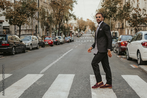 Tablou Canvas Elegant bearded businessman crossing the street