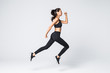 Full length of jumping fitness woman over gray background
