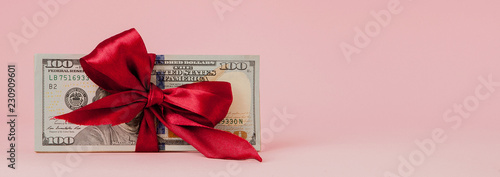 Fototapeta one hundred dollars gift wraped with a red ribbon on pink background obraz