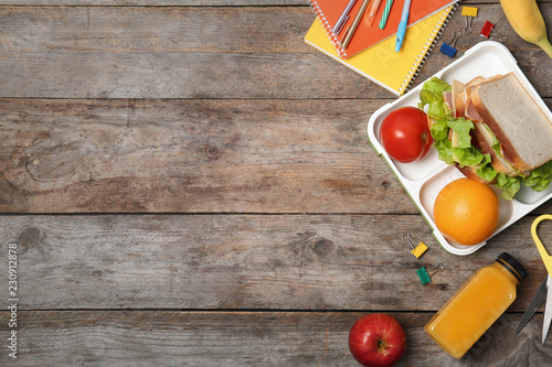 Flat lay composition with healthy food for school child and space for text on wo Fototapet