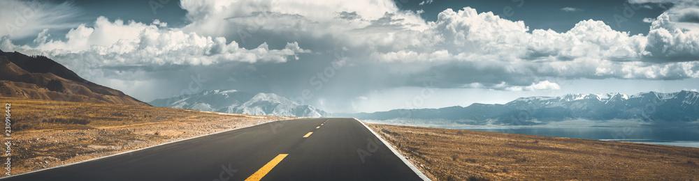 Road to mountain along lake
