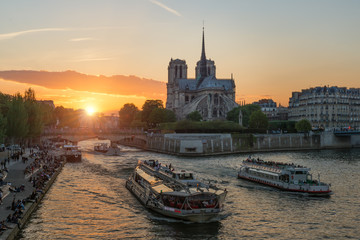 Notre Dame de Paris cathedral with cruise ship in Seine river in Paris, France. Beautiful sunset in Paris, France