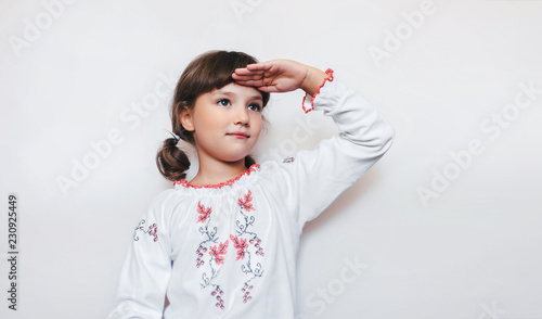 A small Ukrainian girl with a smile looks into the distance. Ukrainian education. Children are patriots.