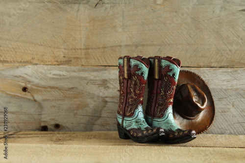 Fotografia, Obraz  cowboy boots and hat isolated on a natural wood background with writing space