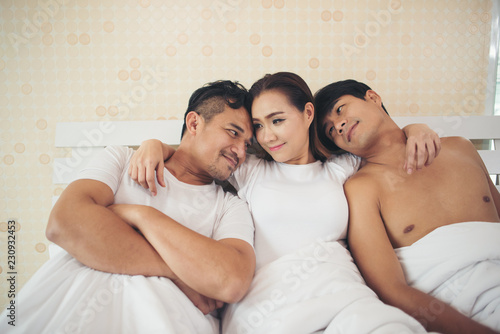 Fotografía  Happy couple having complicated affair and love triangle in bedroom