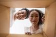 Leinwandbild Motiv Happy couple opening a box and looking inside to product