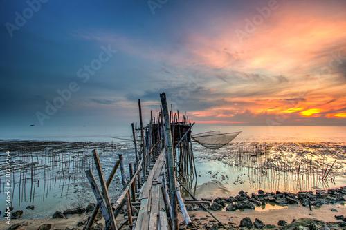 Fototapeta Long exposure image of langgai during beautiful sunset , the traditional fishing medium at Malaysia