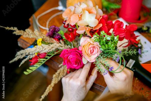 Fotografie, Obraz  Female hands making beautiful bouquet of flowers on background