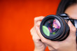 Leinwanddruck Bild - Photography background concept. Closeup of photographer using a camera on red background.