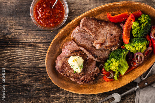 Photo  Grilled Beef steak with garlic butter and vegetables