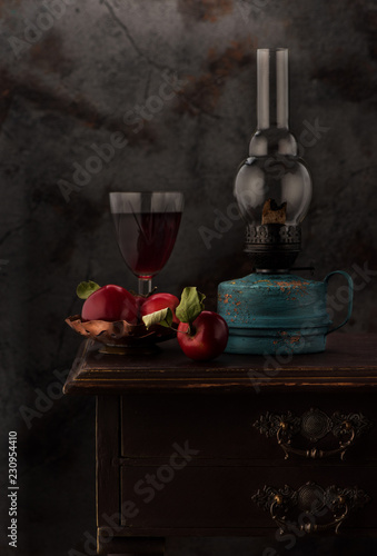 Fototapeta Still life with red wine, vintage oil lamp and apples in a vase obraz