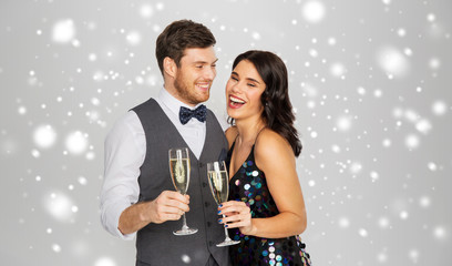 Fototapeta christmas party, new year celebration and holidays concept - happy couple with glasses drinking non alcoholic champagne over grey background and snow