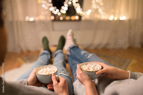 hygge, leisure and christmas concept - close up of couple drinking hot chocolate with marshmallow at home