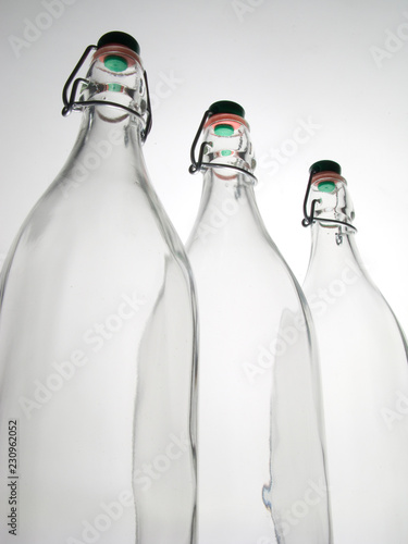 Fotografía  close -up of 3 empty transparent glass bottles of 1 liter with orange and green